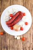 Placa blanca con las salchichas más el queso y la verdura Foto de archivo libre de regalías