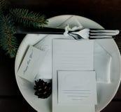 Placa blanca con los cubiertos y las hojas de papel en un fondo de madera inscripción - Feliz Año Nuevo Espacio para el texto tap Fotos de archivo libres de regalías
