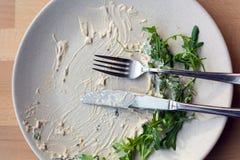 Placa blanca con los remanente de la salsa y de los verdes, en los cuales mienten un cuchillo y una bifurcación fotografía de archivo libre de regalías