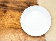 Placa blanca plana en blanco, en de madera marrón con la servilleta, tabla del ranner, visión superior Mofa para arriba, espacio  fotografía de archivo