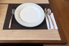 Placa blanca vacía, cuchara inoxidable; cuchillo y bifurcación para el sistema de cena Fotos de archivo