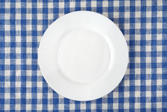 Placa blanca vacía en mantel a cuadros Imagen de archivo