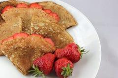 Placa blanca y crepes minúsculas con las fresas Foto de archivo libre de regalías
