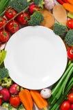 Placa blanca y verduras orgánicas, visión superior vertical del fondo Imagen de archivo libre de regalías