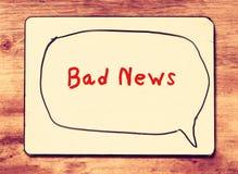 Placa branca com as más notícias da frase escritas nelas, sobre o fundo de madeira imagem filtrada com efeito retro Fotografia de Stock Royalty Free