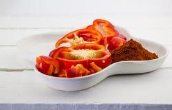 Placa branca com a especiaria vermelha do capsicum e da paprika isolada na oxidação Imagem de Stock Royalty Free