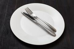 Placa branca com faca paralela, colher na obscuridade Foto de Stock Royalty Free