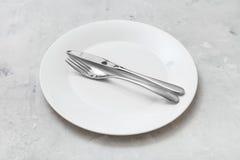 Placa branca com faca paralela, colher no concreto Fotografia de Stock Royalty Free