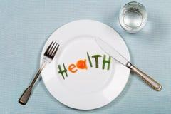 Placa branca com a saúde da palavra feita de partes coloridas de vegetais e de vidro de puro no fundo azul do teblecloth Imagens de Stock Royalty Free