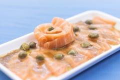 Placa branca com sashimi, alcaparras e shoyu dos salmões imagens de stock