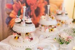 Placa branca de queques coloridos deliciosos na tabela do casamento Imagens de Stock Royalty Free
