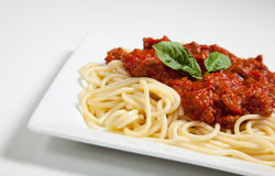 A placa branca do espaguete e a carne sauce com manjericão fotografia de stock royalty free
