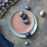 Placa cerâmica vitrificada em uma cor de viver Coral Pantone com os ovos da páscoa violetas pintados em um fundo de pedra cinzent fotografia de stock