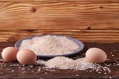 Placa cinzenta vazia com grões do arroz e dos ovos na tabela de madeira Foco seletivo fotos de stock