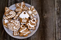 Placa com as cookies do Natal no fundo de madeira, vista superior Fotografia de Stock