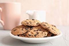 Placa com as cookies saborosos dos pedaços de chocolate e o copo borrado do leite no fundo cinzento fotografia de stock royalty free