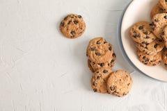 Placa com as cookies saborosos dos pedaços de chocolate no fundo cinzento, vista superior imagem de stock