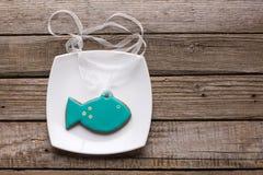 Placa com as cookies saborosos dos peixes na tabela de madeira Fotografia de Stock Royalty Free