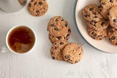 Placa com as cookies saborosos e a xícara de café dos pedaços de chocolate no fundo cinzento imagem de stock