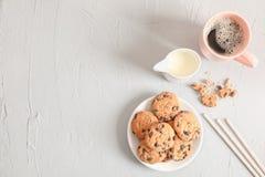 Placa com as cookies saborosos e a xícara de café dos pedaços de chocolate no fundo cinzento, vista superior foto de stock