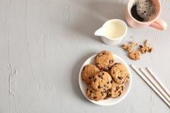 Placa com as cookies saborosos e a xícara de café dos pedaços de chocolate no fundo cinzento, vista superior fotografia de stock