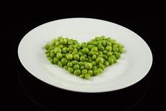 Placa com as ervilhas dadas forma como um coração Fotos de Stock Royalty Free
