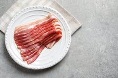 Placa com as fatias de toucinho cruas do bacon foto de stock royalty free