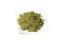 Placa com as folhas de chá secas verdes frouxas, isoladas imagem de stock royalty free