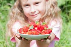 Placa com as morangos nas mãos da menina Fotos de Stock Royalty Free