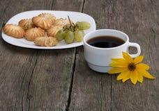 Placa com cookies, uma xícara de café e uma flor amarela, ainda Imagem de Stock Royalty Free
