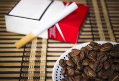 Placa com feijões de café na frente de um cigarro Fotos de Stock Royalty Free