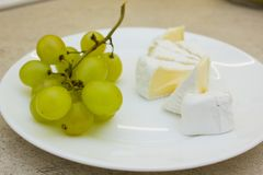 Placa com grupo de uvas e de partes verdes do queijo Imagem de Stock