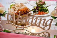 A placa com o grupo do casamento da inscrição na tabela servida dos recém-casados fotos de stock