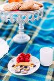 A placa com os doces do bolo e do chocolade da morango da esponja é colocada entre a vela e o varrão pequenos brancos com Imagem de Stock
