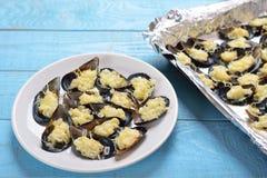 Placa com os mexilhões cozidos com queijo e cebolas Imagem de Stock
