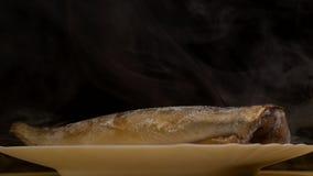Placa com os peixes congelados da cavala em um fundo preto de que há um frescor gelado e uma evaporação, close-up, 4K filme