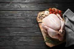 Placa com peru e os ingredientes crus no fundo de madeira imagens de stock