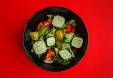 Placa com salada no fundo vermelho Fotografia de Stock Royalty Free