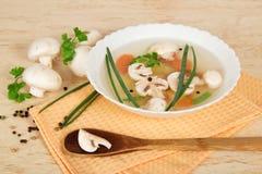 Placa com sopa, uma colher de madeira, cogumelos de campo Imagem de Stock