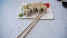 Placa com sushi fresco Rolls em um restaurante japonês em uma tabela de madeira branca à moda Tiro da zorra video estoque