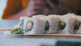 Placa com sushi fresco Rolls em um restaurante japonês em uma tabela de madeira branca à moda Tiro da zorra vídeos de arquivo
