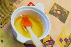 Placa con aceite de oliva y un cepillo Fotos de archivo