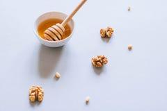 Placa con el cazo de la miel, las nueces y las nueces de pino Imágenes de archivo libres de regalías