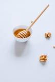 Placa con el cazo de la miel, las nueces y las nueces de pino Fotografía de archivo libre de regalías