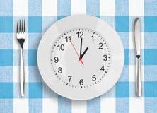 Placa con el clockface - concepto del tiempo del almuerzo Imágenes de archivo libres de regalías