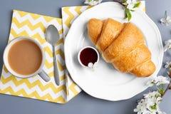 Placa con el cruasán, el atasco y la taza de café sabrosos en la tabla Imágenes de archivo libres de regalías
