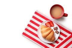 Placa con el cruasán y la taza de café sabrosos Fotos de archivo libres de regalías