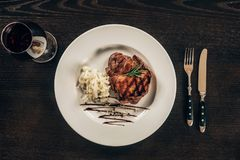 Placa con el filete de carne de vaca y el vidrio de vino rojo en la tabla Imágenes de archivo libres de regalías