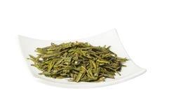 Placa con el té seco verde flojo, aislado Imagen de archivo libre de regalías