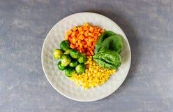 Placa con la col, las zanahorias, el ma?z y la espinaca Consumici?n sana imágenes de archivo libres de regalías